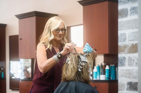 Susan, a stylist at Panache Hair Salon in Shelton, CT, highlights a client's hair.