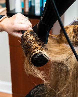 A stylist blowdrying hair at Panache Hair Design in Shelton, CT.