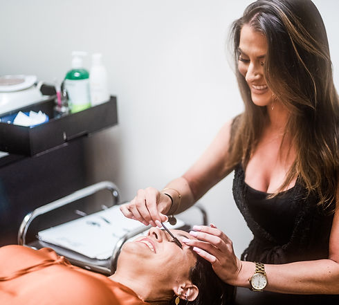 A certified eyelash technician at Panache Hair Design in Shelton, CT doing eyelash extensions on a client.