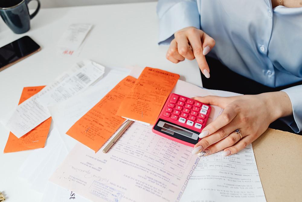 Imagem de uma pessoa com uma mesa com papéis e uma calculadora - Como ter uma política de remuneração adequada na escola?