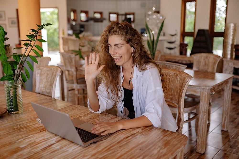 Mulher interagindo com pessoa por meio de notebook. Atendimento humanizado nas escolas. Gestão Escolar eficaz.