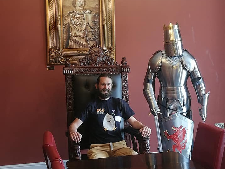 A guest posing in the Llewelyn Room throne next to the armour.