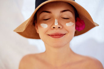 Woman smile applying sun cream  on face.