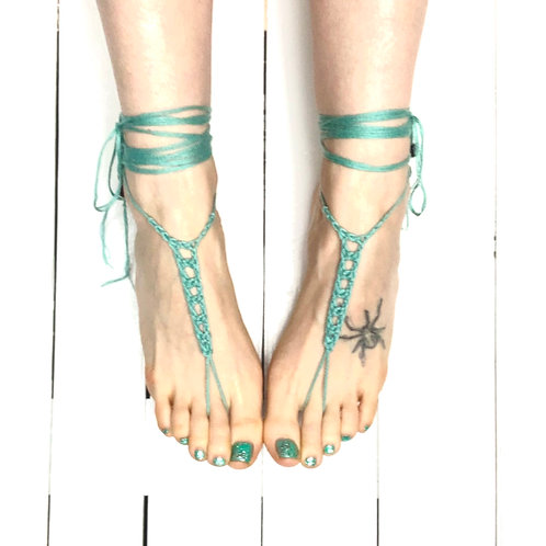 Turquoise organic cotton barefoot sandals with glass beads on 2 feet on white shiplap background