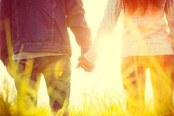Nainen ja mies pitävät kädestä kiinni auringossa