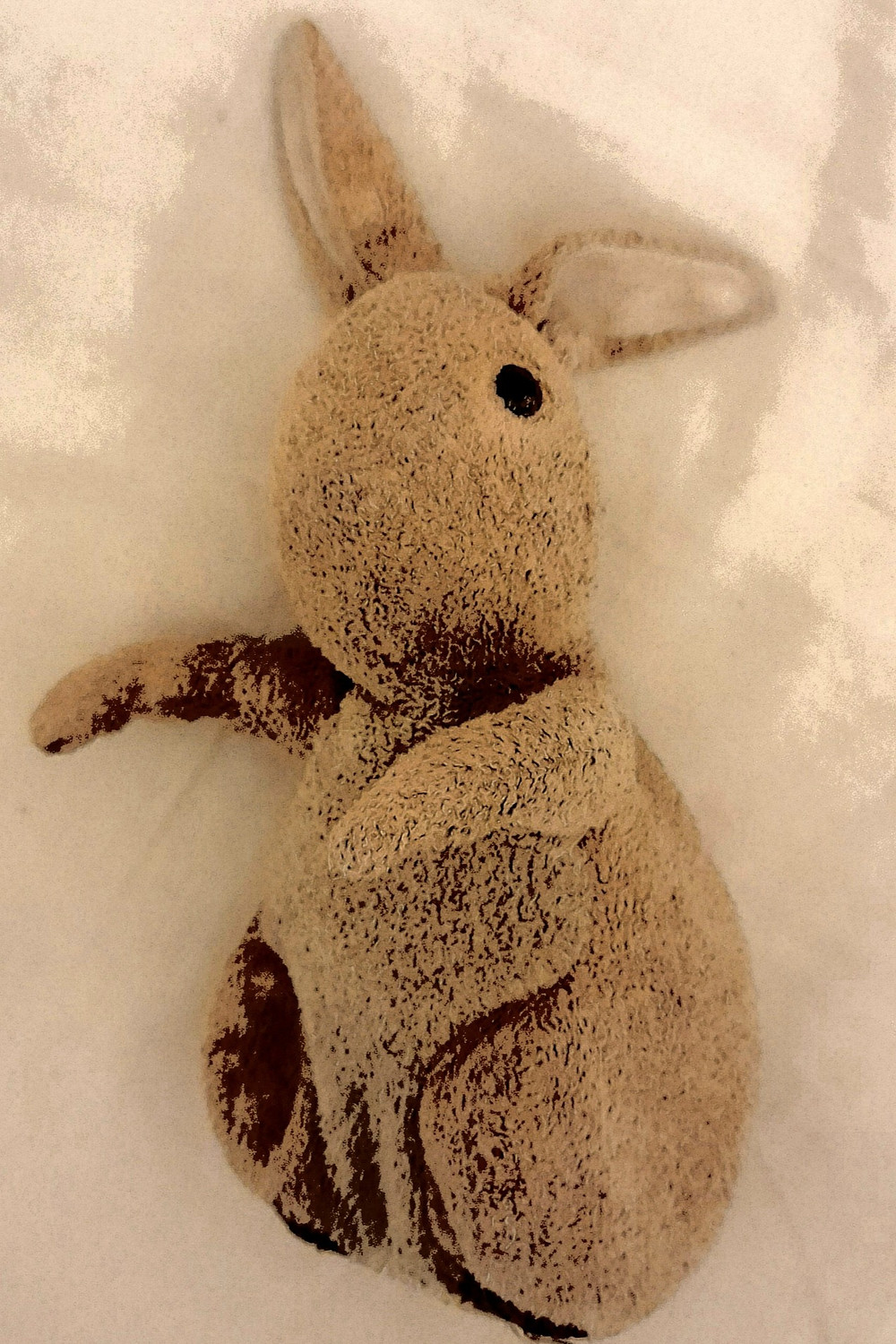 An old stuffed bunny rabbit teddy, lain on a white duvet