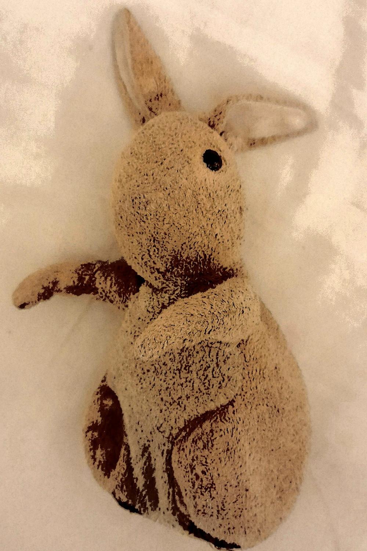 An old stuffed bunny rabbit teddy, lain on a white duvet