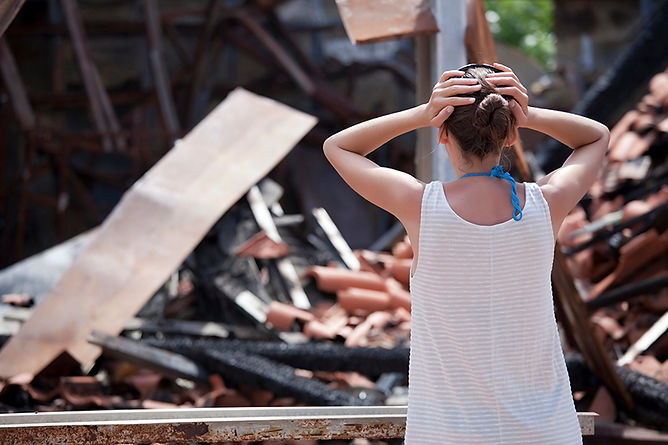 upset woman at destroyed house,  what to do after a house fire, common causes of house fires, steps after a house fire, how to recover from a house fire