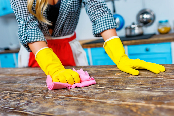 Restoring Water Damaged Furniture Woman Wiping Off Dirt From Wooden Table, restoring water-damaged furniture, water damaged furniture help, fix wet furniture