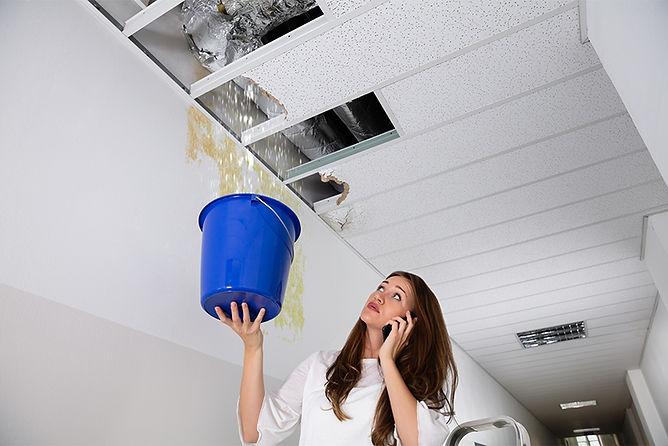 woman catching water leak, ceiling leaking, ceiling water damage, roof leak