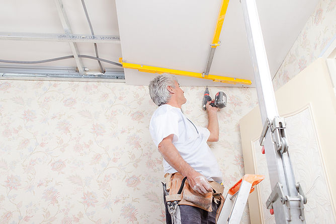 man fixing ceiling, water damage from heavy rain, storm home water damage, home rain water damage, prevent rain water damage