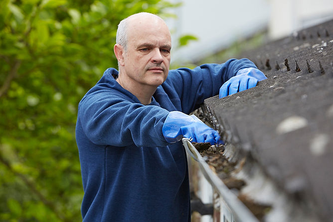 man cleaning gutter, water damage from heavy rain, storm home water damage, home rain water damage, prevent rain water damage
