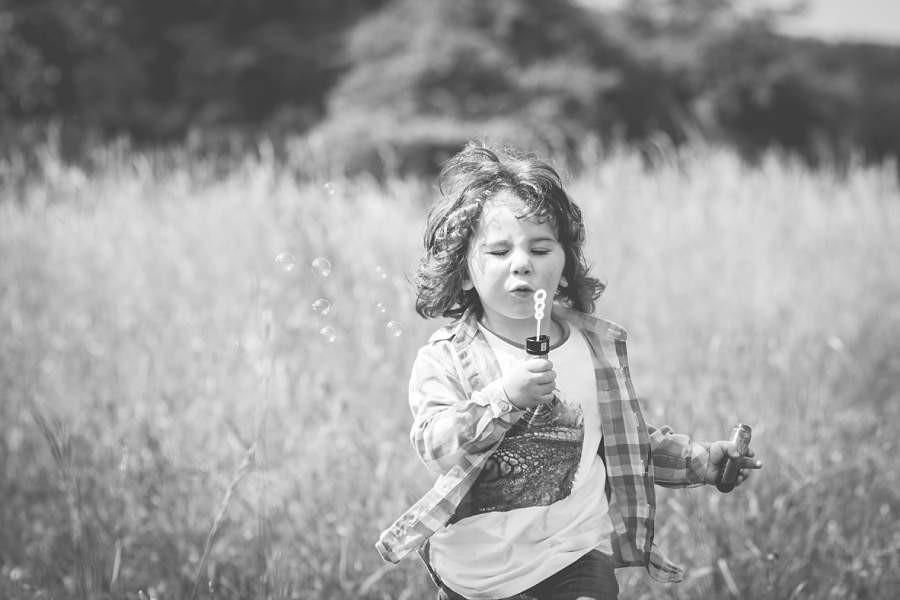Junge rennt durchs Gras - frühlingshafte Kinderfotos