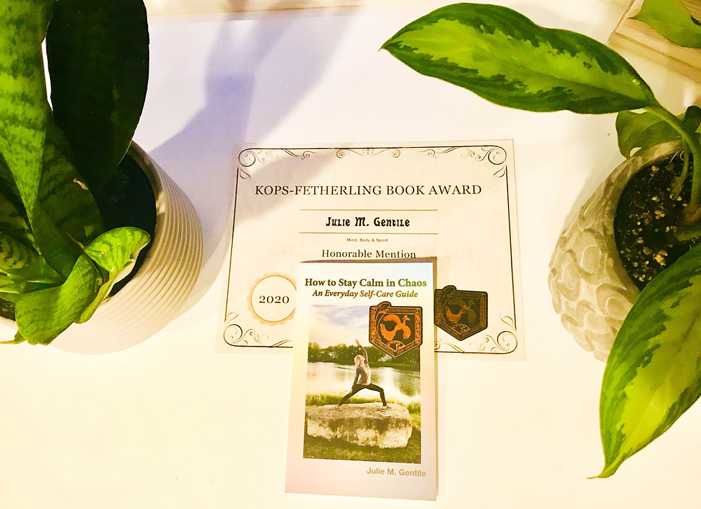 Julie M. Gentile's book How to Stay Calm in Chaos: An Everyday Self-Care Guide with Kops-Fetherling International Book Awards certificate and two plants