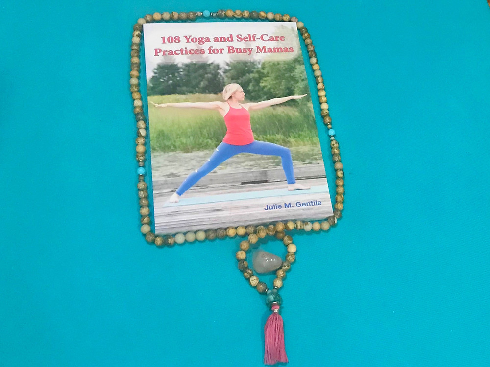 Julie M. Gentile's book 108 Yoga and Self-Care Practices for Busy Mamas on a yoga mat with mama beads around it.