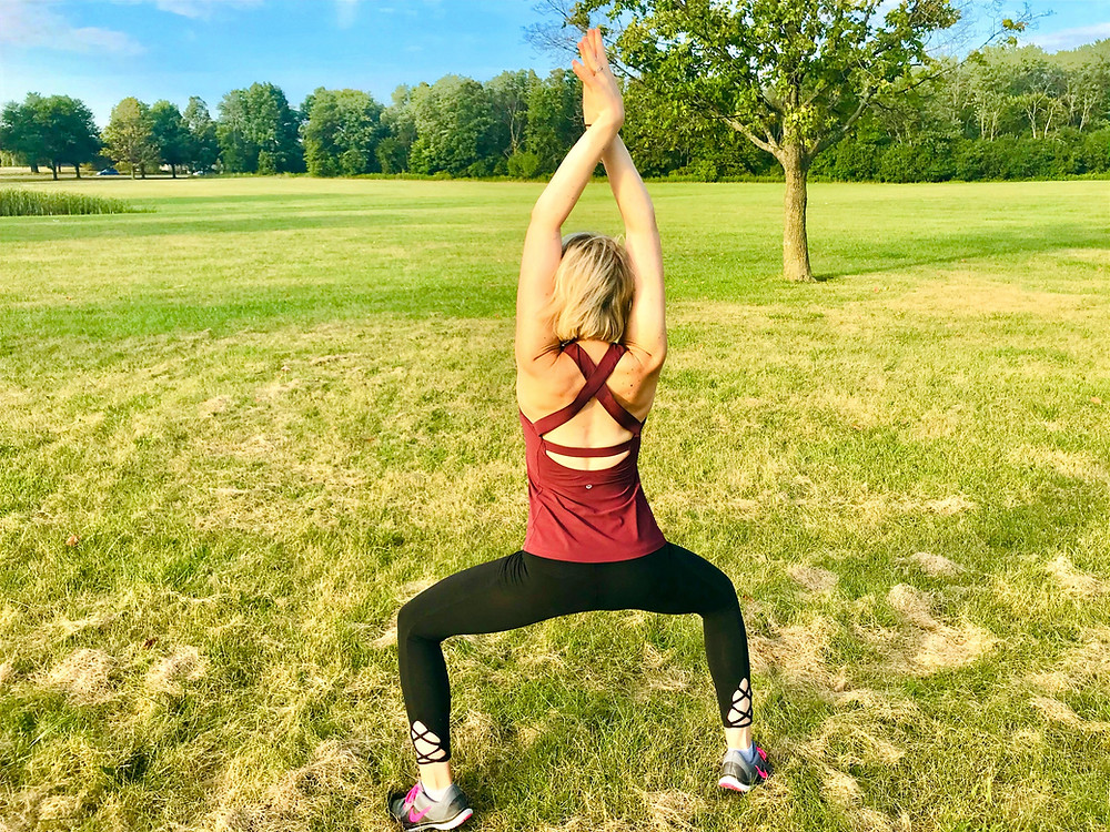 Julie M. Gentile in a standing yoga pose on the grass with knees bent and arms up looking out into the trees and sky