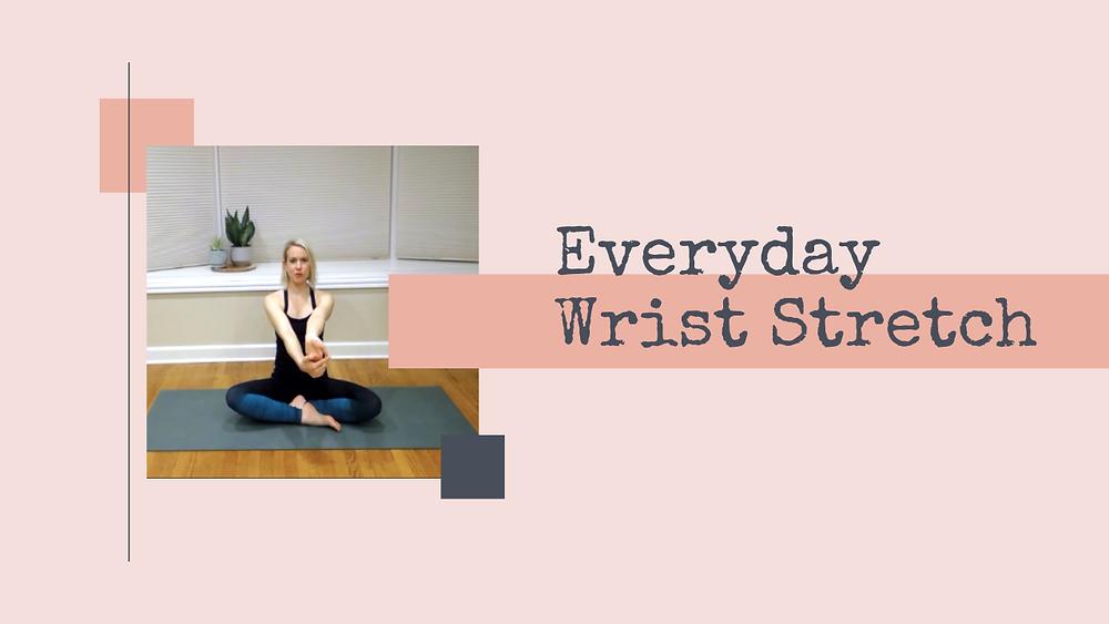 Julie M. Gentile seated on a yoga mat in wrist stretch