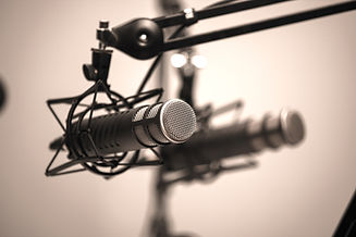 Shallow depth of field shot of two professional podcasting microphones on boom arms_edited.jpg