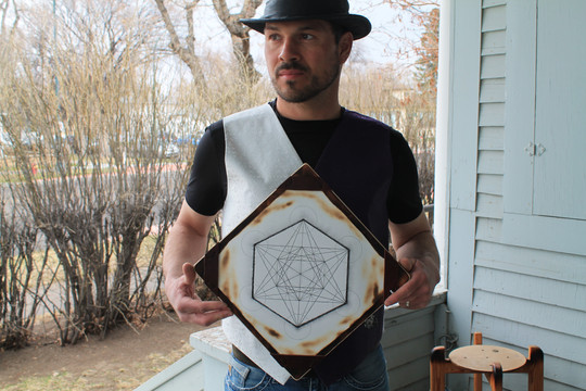 Bob holding hand drawn metatrons cube on handmade frame