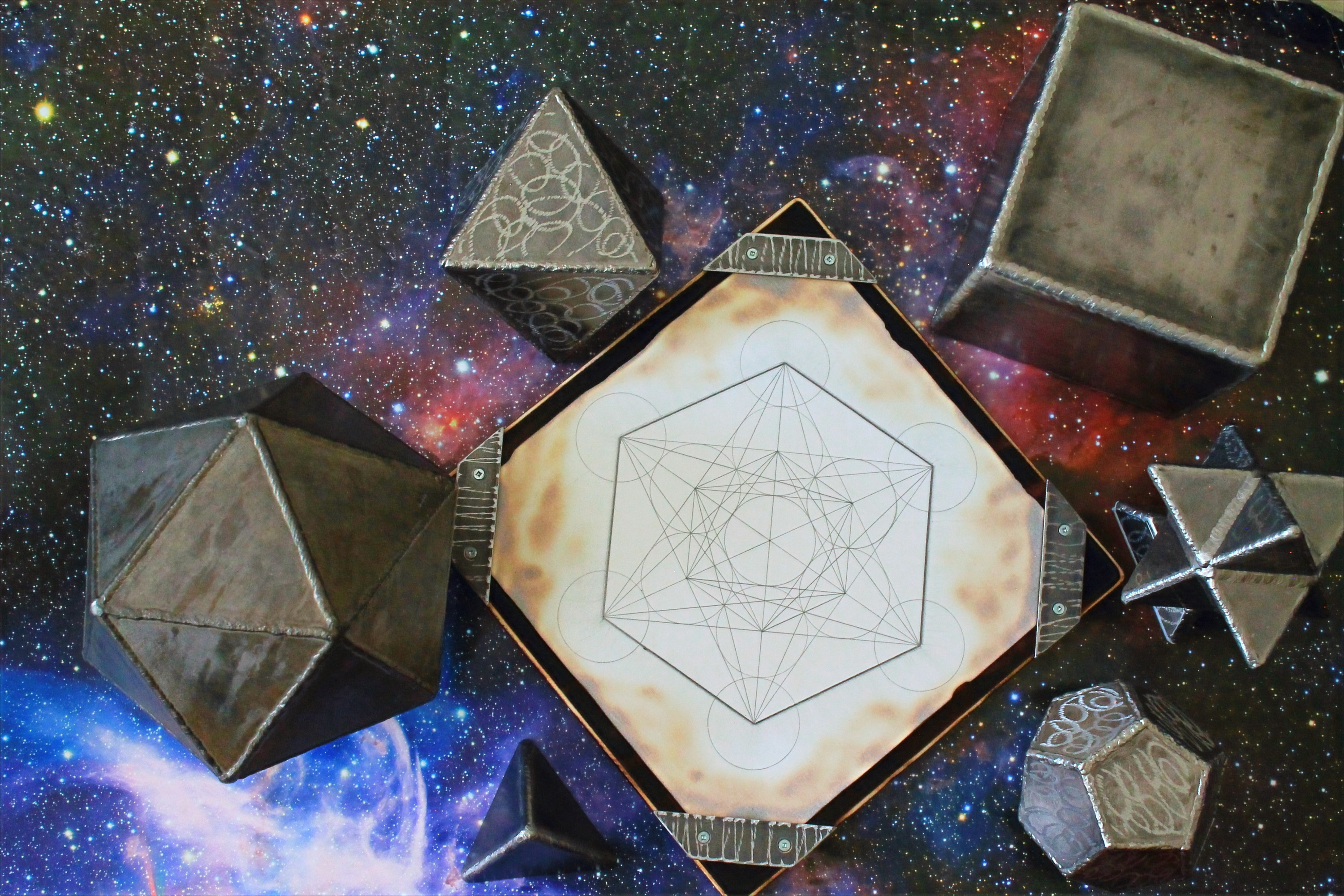 Bob;s complete collection of hand made sacred geometry metal decor, with a hand drawn metatron's cube.