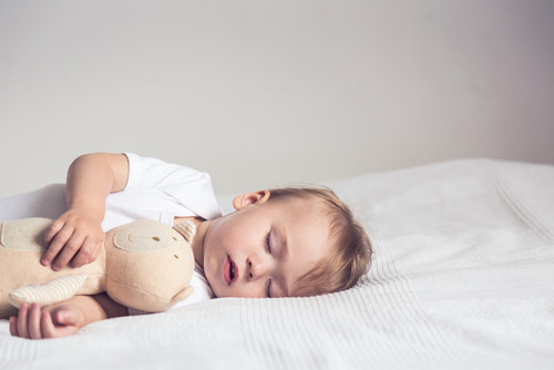 Sleeping baby in bed, holding a stuffed bear