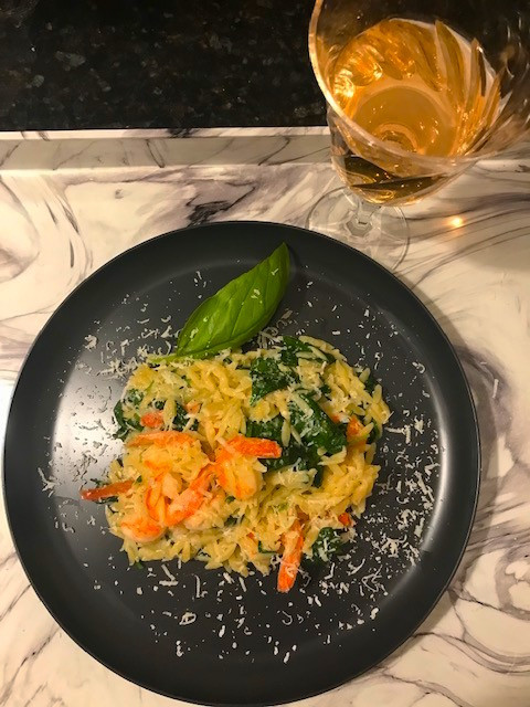 orzo with shrimp, spinach and Parmesan cheese on a black plate garnished with basil. A glass of rose wine sits on the tabletop.