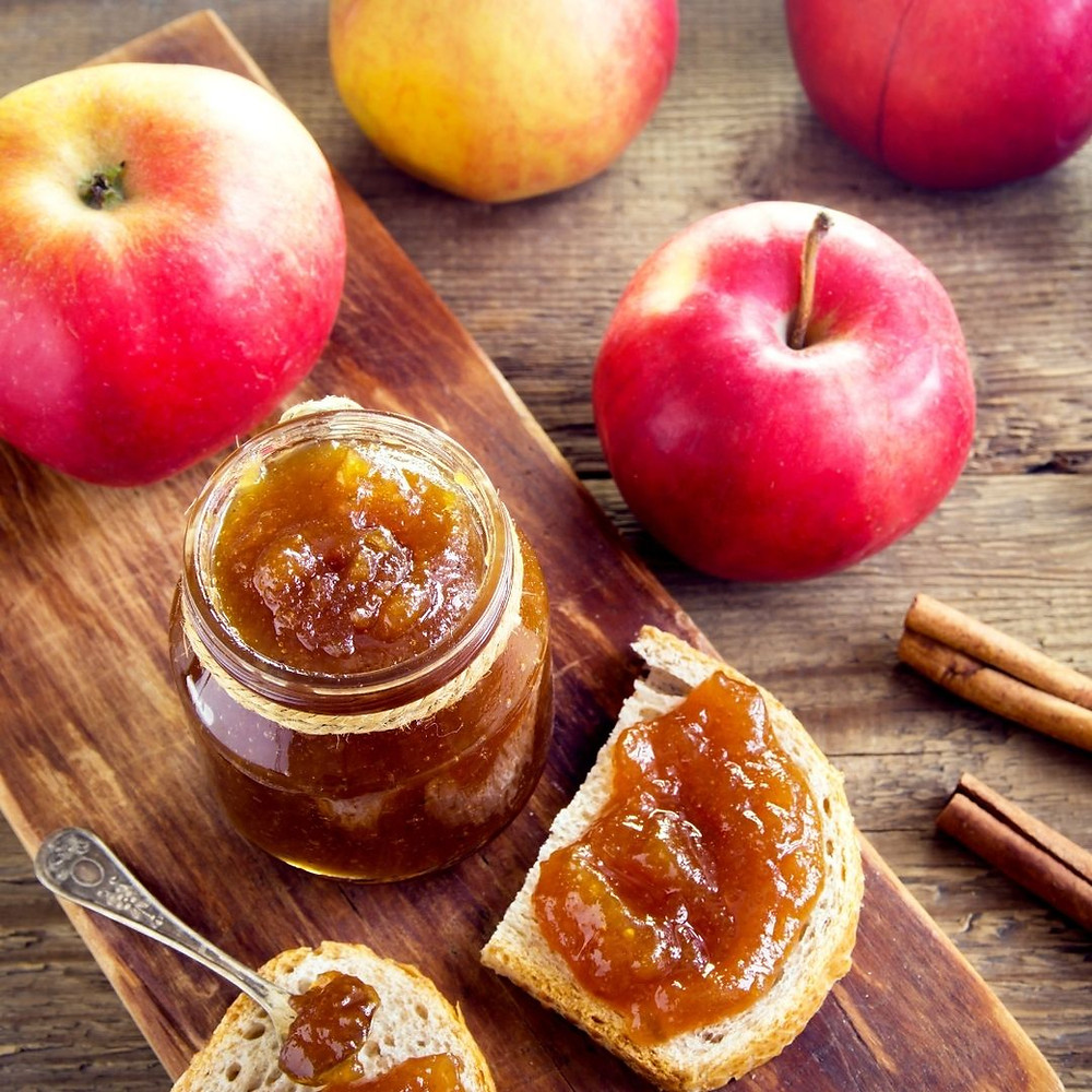 apples, apple butter in jar and apple butter spread on rye bread