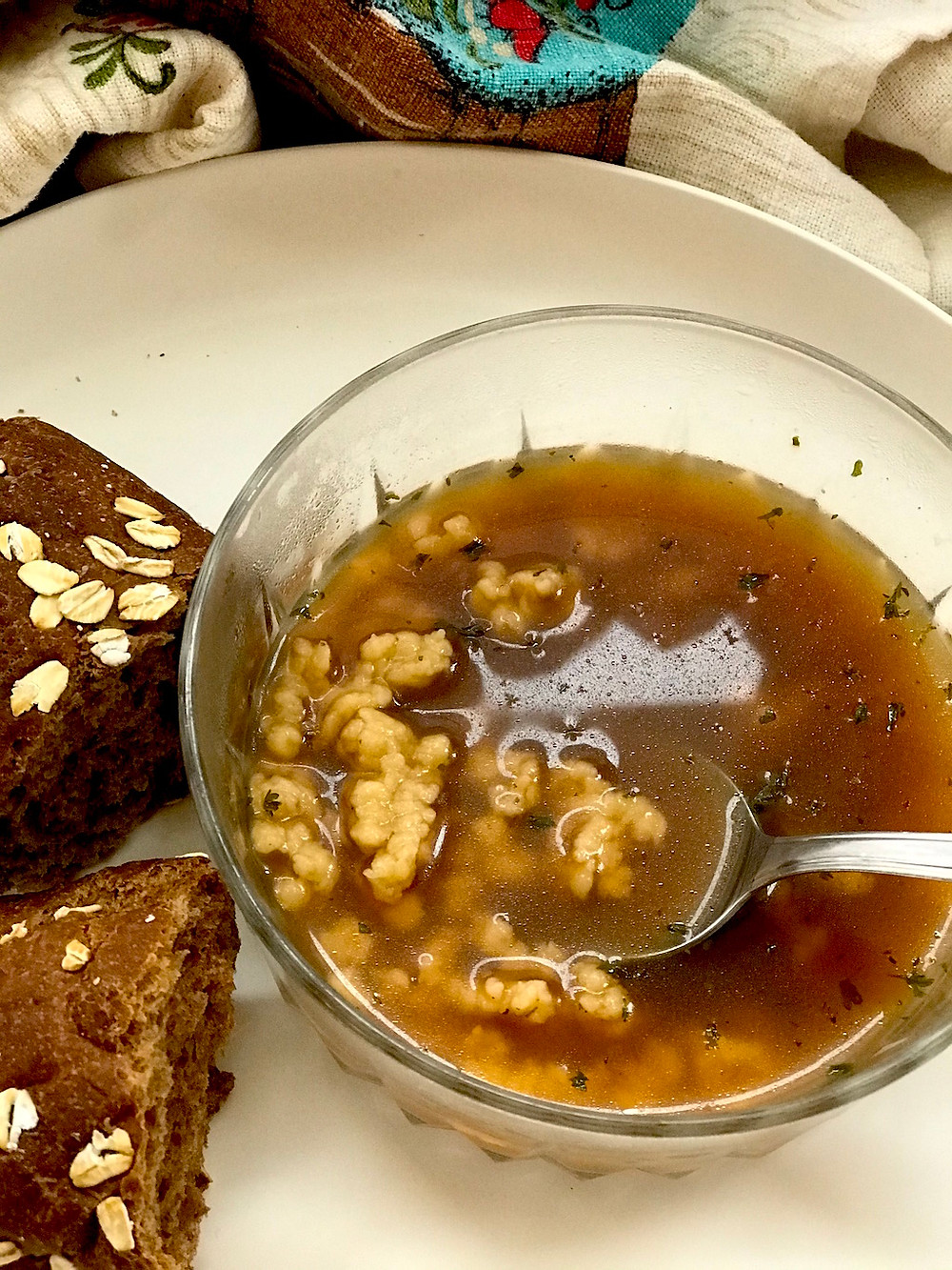 Beef broth with tiny dumplings in a glass bowl with brown bread on plate.