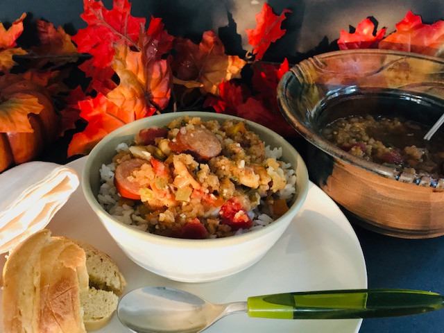 bowl of gumbo over rice on table with decorative leaves in background