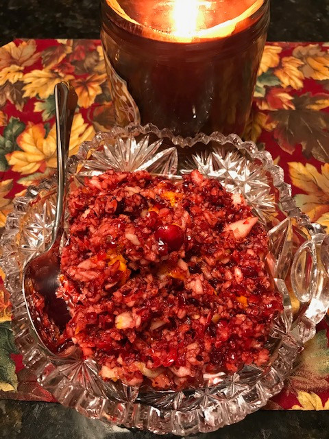 fresh cranberry relish in a crystal bowl with a candle in background on an autumn tablecloth.