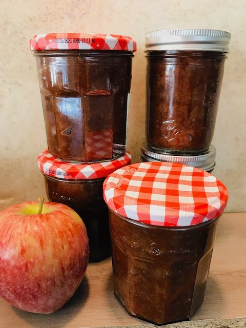 Four pint-sized jars of apple butter with an apple