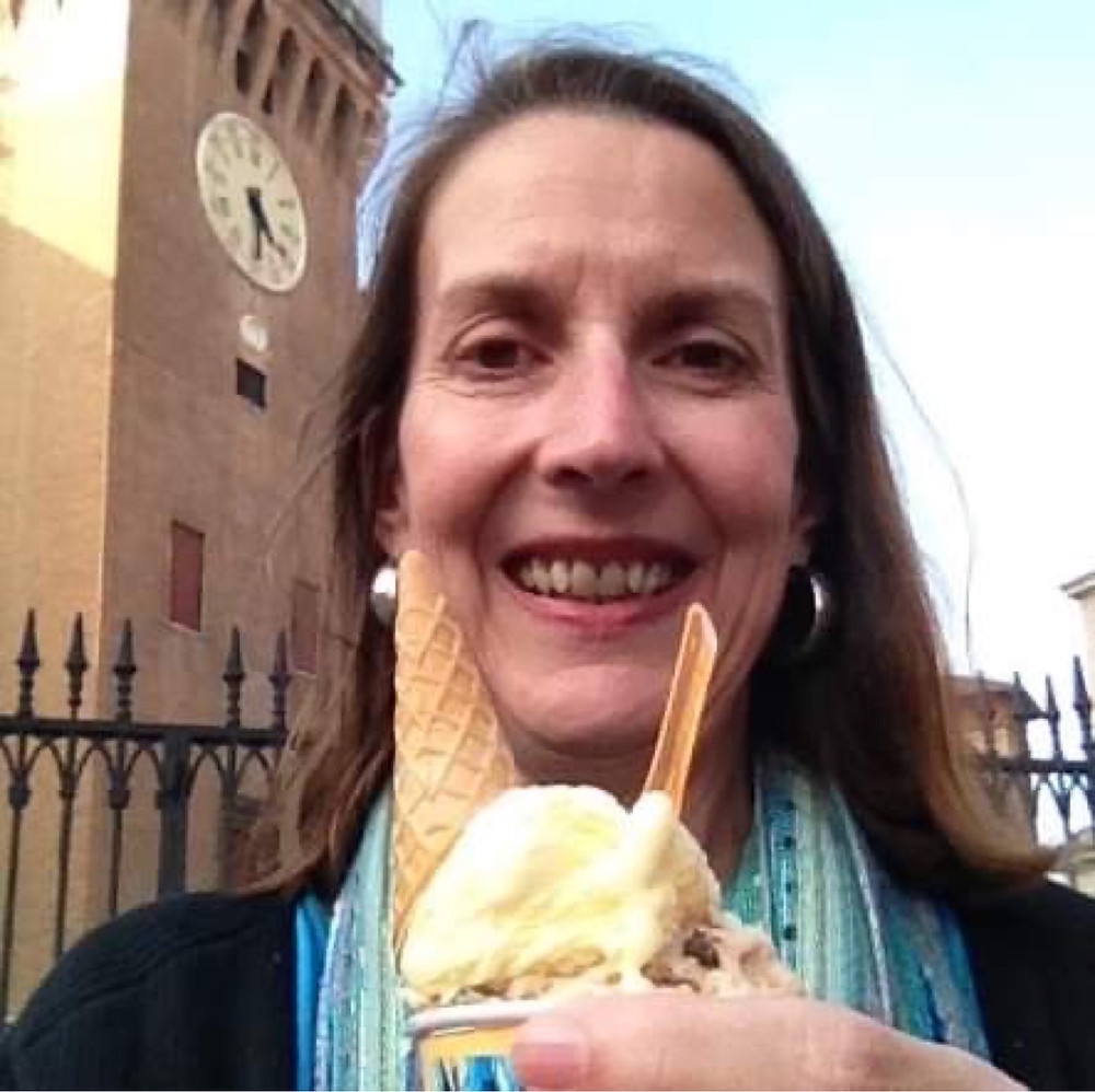 woman with long brown hair holds cup of lemon ice cream