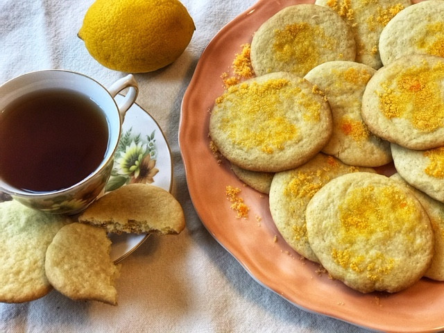 Butter and lemon cookies on a pink plate with a cup of tea.