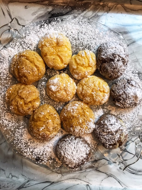 round cookies on a glass plate dusted with powdered sugar