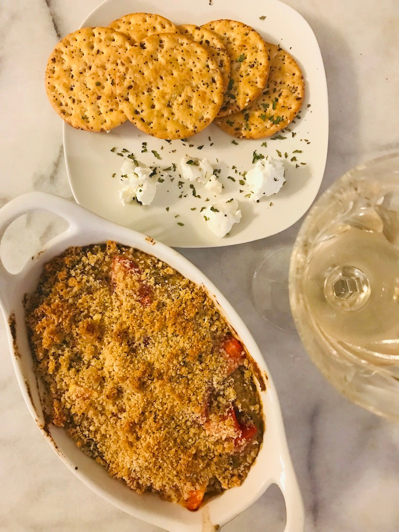 baking dish with eggplant dip and crackers on a white plate with a glass of wine