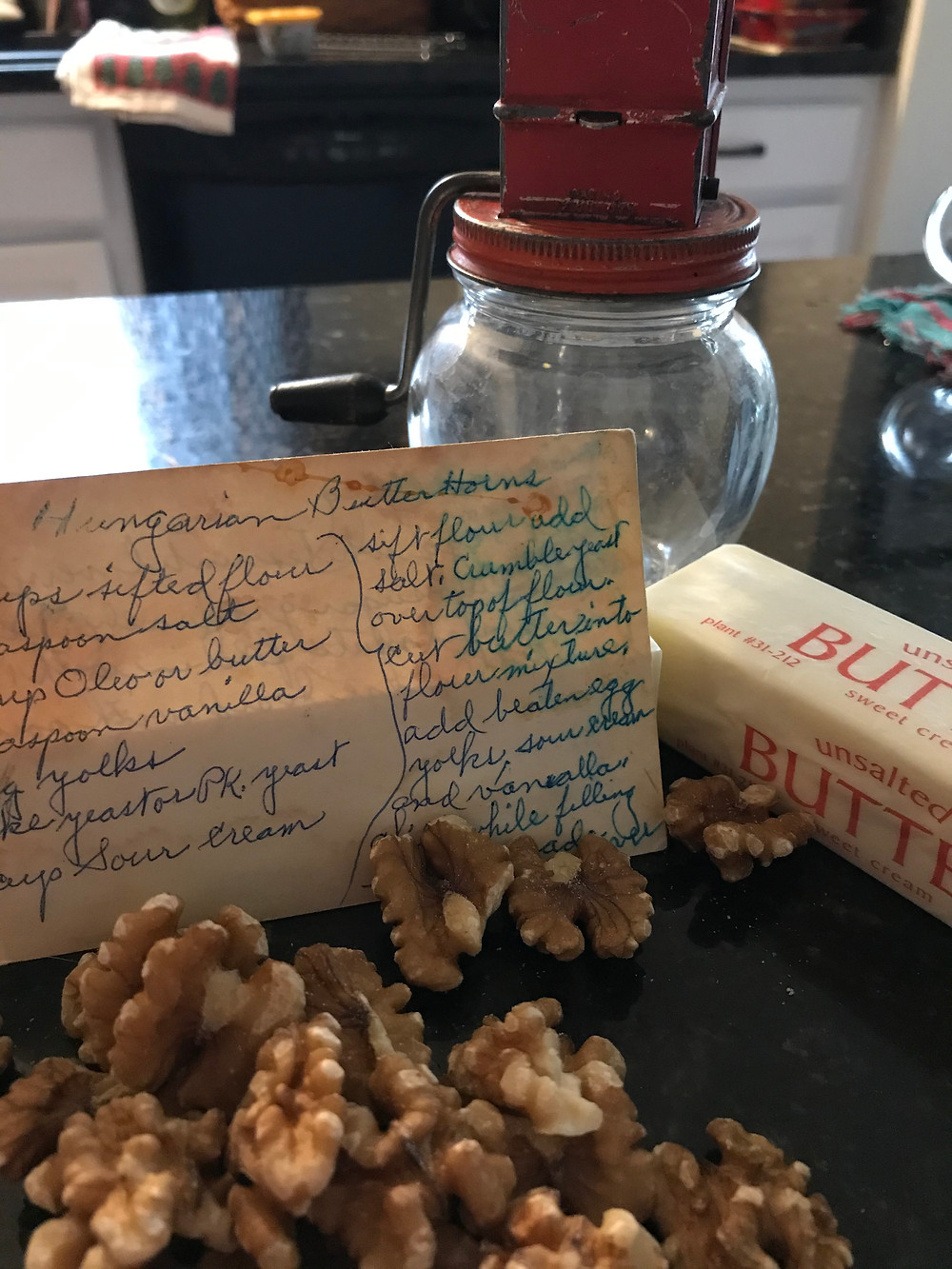 walnuts in front of a recipe card, stick of butter and vintage nut grinder
