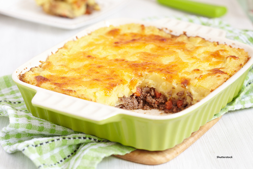 ground beef and mashed potatoes in a green baking dish
