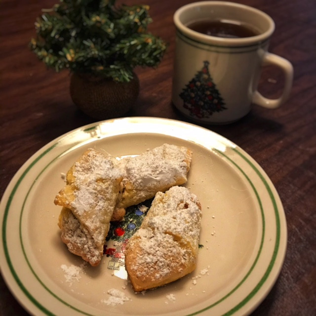 crescent shaped cookies with powdered sugar sitting on a Christmas plate