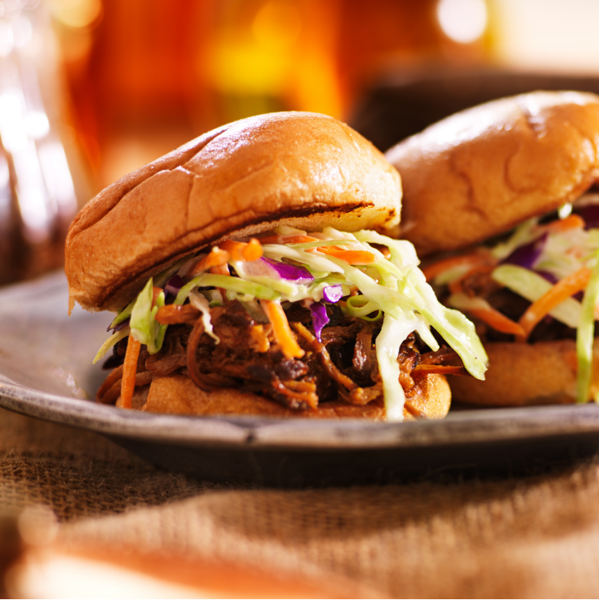 beef sandwiches topped with cole slaw on toasted buns