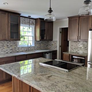 Warm stained cabinets with gray countertops, and farmhouse lights gives this a modern feel