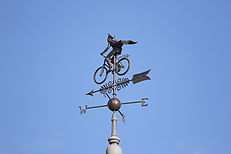 contemporary weather vane on a clock tow