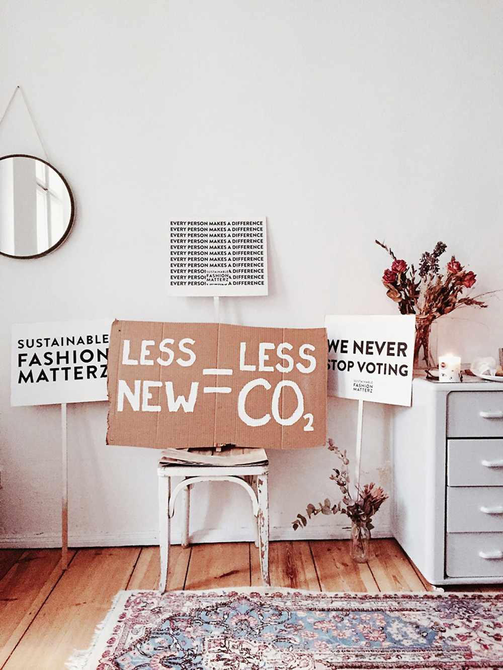 A carboard piece put on a chair that says: Less New = Less CO2. There are also other boards saying: Sustainable Fashion Matterzz and We never stop voting