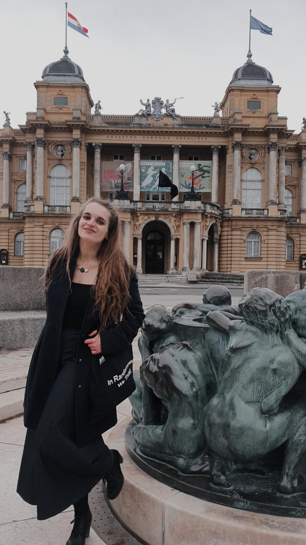 Tena in a long black dress and dark blue coat, standing in front of a National Theathre building in Zagreb, Croatia