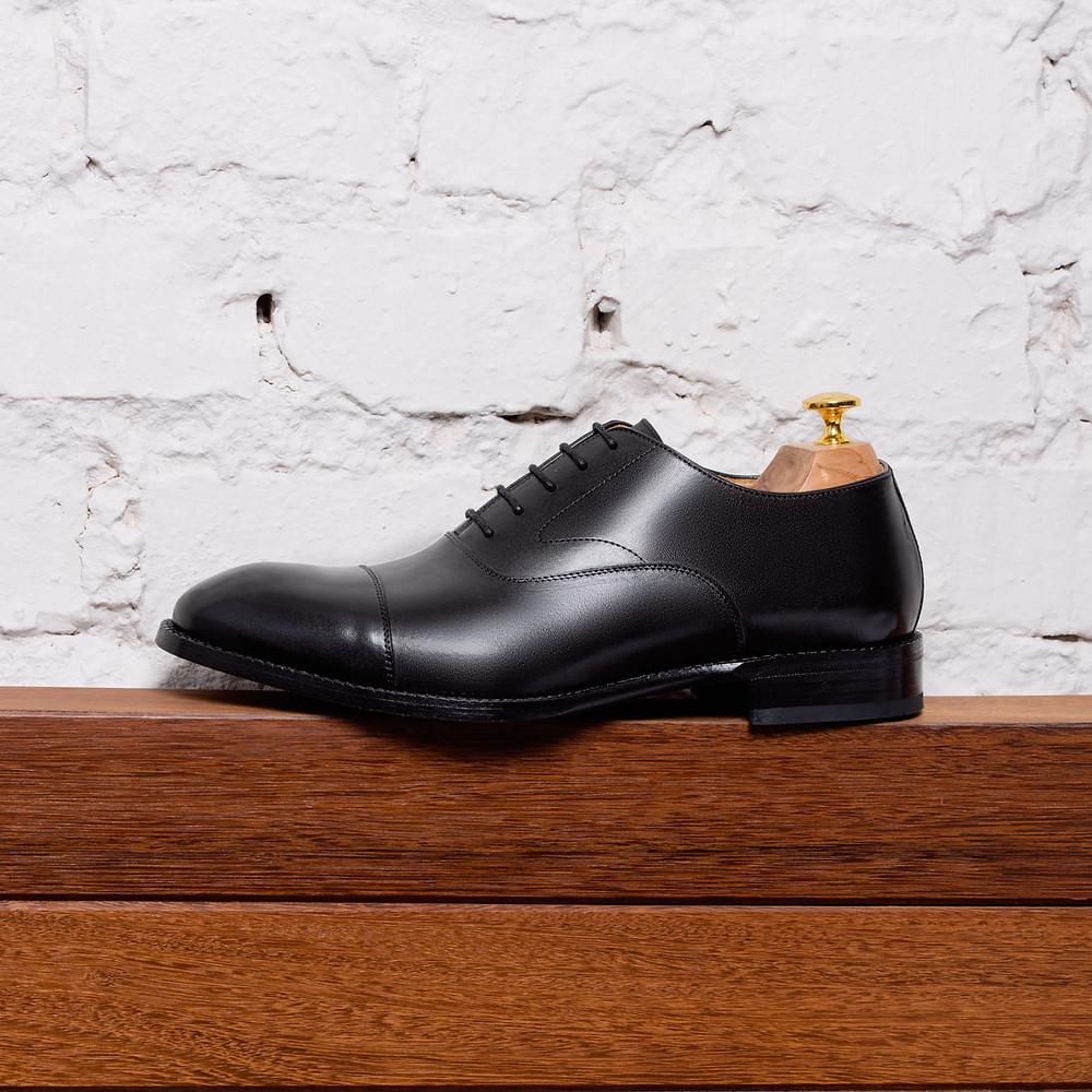 Beckett Simonon black dress shoee displayed on a wooden shelf