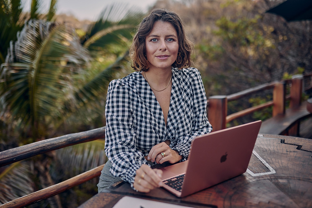 What does a success mean? Is it about making money or something more? Photo of Nikki Trott sittin behind a laptop on a balcony.