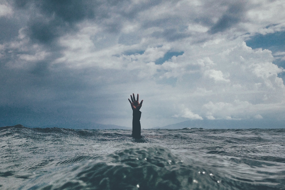 Person's hand sticking out of sea, as a sign of help