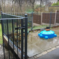 Black railings in a garden with paddling pool - Copy.PNG