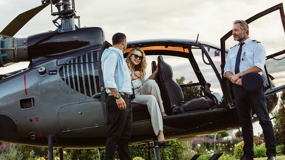 Couple stepping out of helicopter