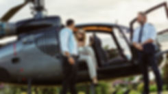 Elegant couple stepping out of helicopter, weekend getaways in South Wales