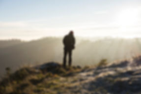Man standing on hill, luxury getaways in Wales
